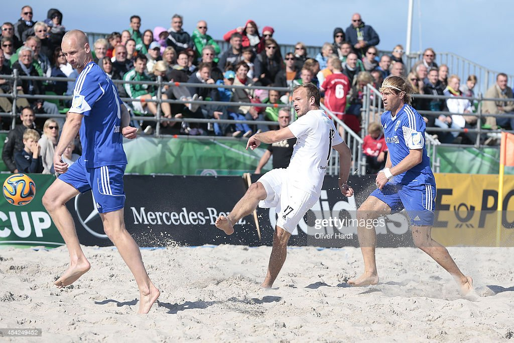 Players of Chemnitz (C)challenges a player of Rostock (R) during the final match between BST Chemnitz and Rostocker Robben on day one of the DFB Beachscoccer Cup at the beach of Warnemunde on August 24, 2014 in Warnemunde, Germany.