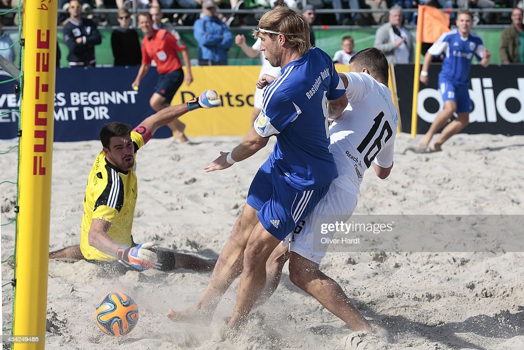 Players of Chemnitz (R) challenges a player of Rostock (L) during the final match between BST Chemnitz and Rostocker Robben on day one of the DFB Beachscoccer Cup at the beach of Warnemunde on August 24, 2014 in Warnemunde, Germany.
