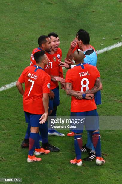 Players of Chile argue with referee Wilmar Roldan during the Copa America Brazil 2019 Semi Final match between Chile and Peru at Arena do Gremio on...