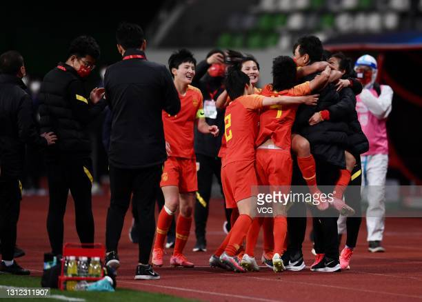 Players of China celebrate victory with head coach Jia Xiuquan after the Tokyo Olympics Women's Football Asian Final Qualifier 2nd leg match between...