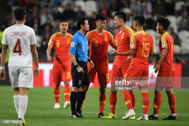 Players of China protest to referee Hiroyuki Kimura of Japan during the AFC Asian Cup Group C match between the Philippines and China at Mohammed Bin...