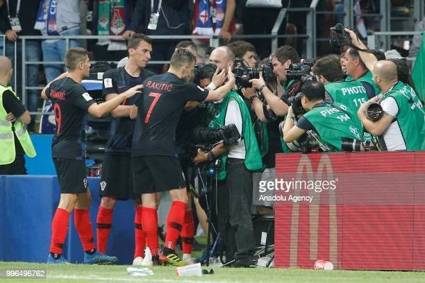 Players of Croatia lift a photojournalist who fell as Croatian players celebrate the goal during the 2018 FIFA World Cup Russia semi final match...