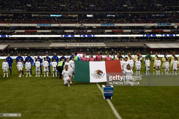 Players of Cruz Azul and America sing the National Anthem during the first round of final of the Mexican Apertura tournament football match at the...