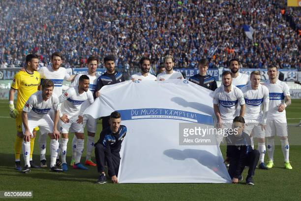 Players of Darmstadt pose with a giant jersey to remember former fan Jonathan Heimes prior to the Bundesliga match between SV Darmstadt 98 and 1 FSV...