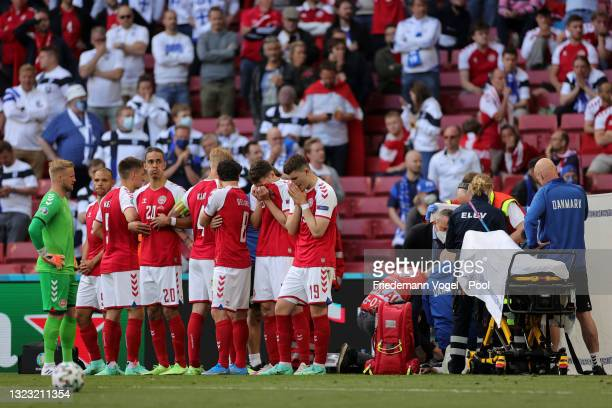 Players of Denmark stand dejected as Christian Eriksen of Denmark receives medical treatment during the UEFA Euro 2020 Championship Group B match...