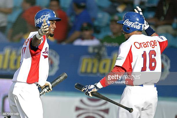 Players of Dominican Republic's Tigres de Licey celebrate after scoring against Mexico's Naranjeros de Hermosillo during their 2014 Caribbean...