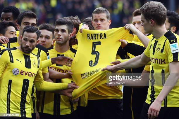 Players of Dortmund hold the jersey of their injured team mate Marc Bartra after winning the Bundesliga match between Borussia Dortmund and Eintracht...