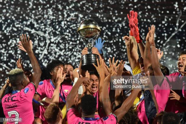 Players of Ecuador's Independiente del Valle celebrate on the podium with the trophy after winning the Copa Sudamericana final football match by...