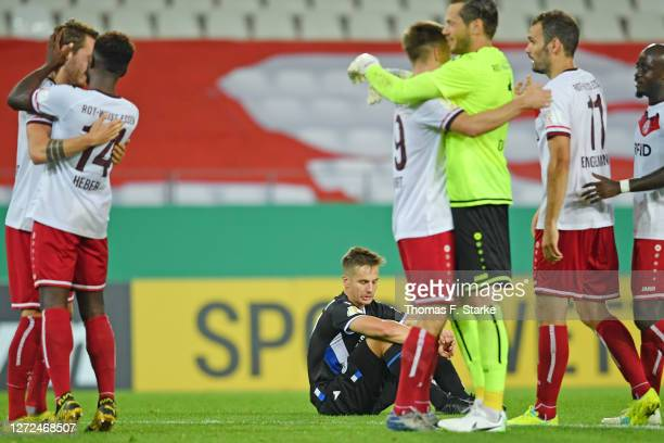 Players of Essen celebrate while Cedric Brunner of Bielefeld looks dejected after the DFB Cup first round match between Rot-Weiss Essen and DSC...