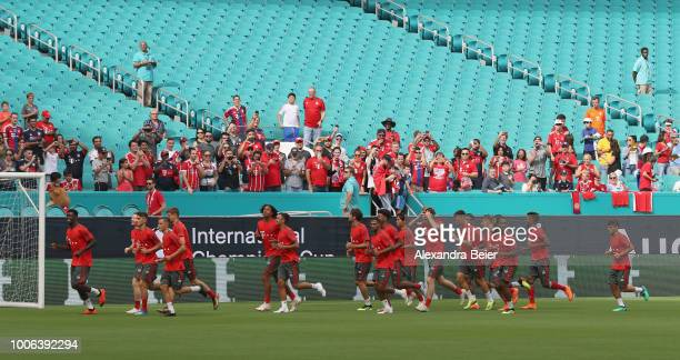 Players of FC Bayern Muenchen warm up in front of fans watching them during a training session ahead of the team's friendly match aganst Manchester...