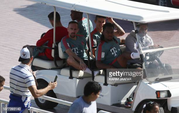 TOPSHOT Players of FC Bayern Munich ride in a cart as they pass by fans in a training session during their winter training camp at the Aspire Academy...