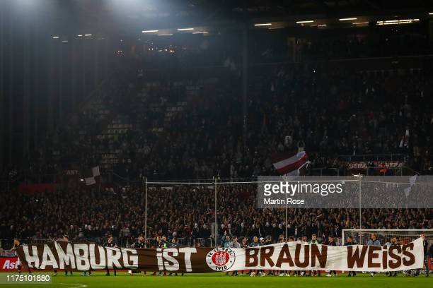 Players of FC St. Pauli celebrate with fans after winning the Second Bundesliga match between FC St. Pauli and Hamburger SV at Millerntor Stadium on...