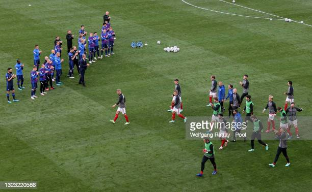 Players of Finland applaud the players of Denmark as they return to the pitch to warm up before play resumes during the UEFA Euro 2020 Championship...