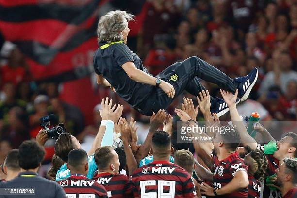 Players of Flamengo hold the coach Jorge Jesus after winning the Brasileirao 2019 after the match against Ceará at Maracana Stadium on November 27...