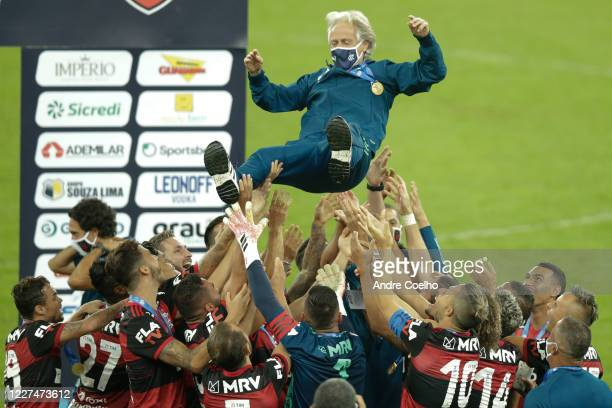 Players of Flamengo lift Head coach Jorge Jesus in the air after winning a second leg match against Fluminense as part of the Campeonato Carioca...