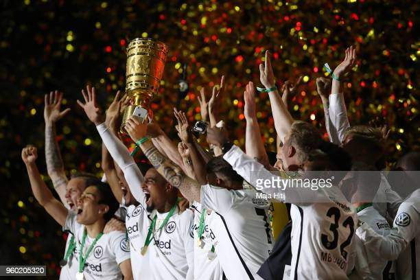 Players of Frankfurt lift the German DFB Cup trophy in the air and celebrate after the DFB Cup final between Bayern Muenchen and Eintracht Frankfurt...