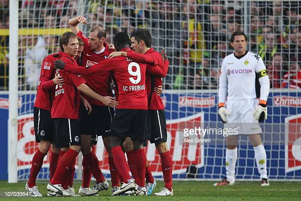 Players of Freiburg celebrate and goalkeeper Roman Weidenfeller of Dortmund reacts after Mats Hummels of Dortmund scored an own goal during the...