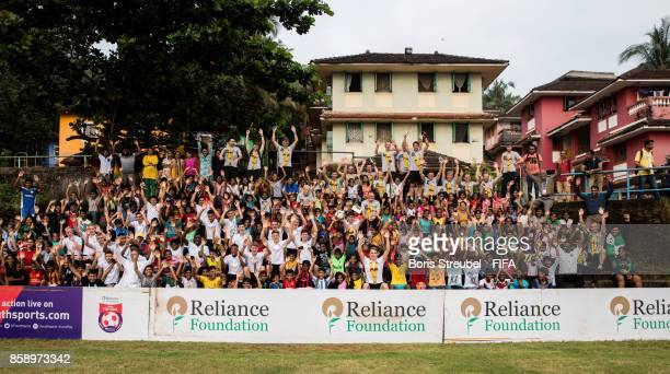 Players of Germany and kids from the orphanage pose for a group picture as the team of Germany visit the Agnel Technical Education Complex during the...