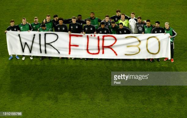 Players of Germany hold a sign saying 'We for 30' for the human rights movement prior to the FIFA World Cup 2022 Qatar qualifying match between...