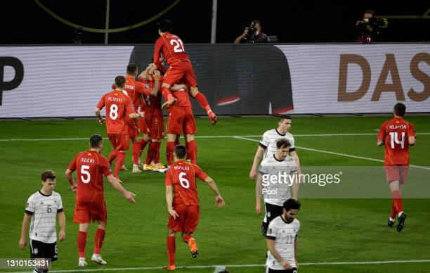 Players of Germany react after conceding as Goran Pandev of North Macedonia celebrates with team mates after scoring their side's first goal during...