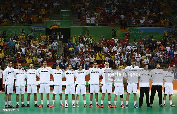 Players of Germany stand for their national anthem ahead of the Men's Preliminary Group B match between Sweden and Germany at on Day 2 of the Rio...