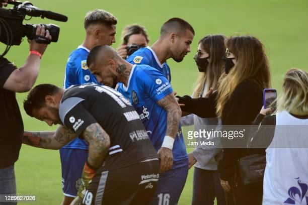 Players of Gimnasia y Esgrima offer condolences to Dalma and Gianinna Maradona daughters of the late former football star Diego Maradona prior a...