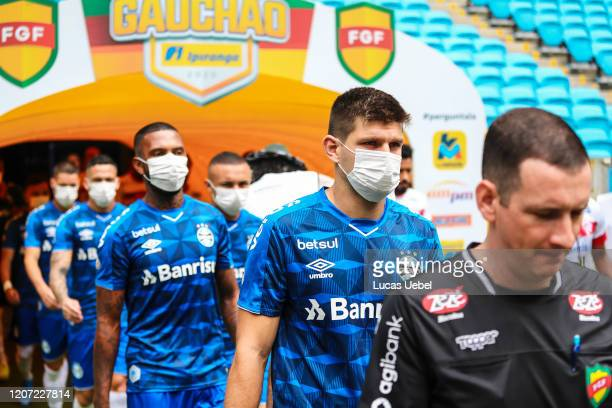Players of Gremio enter the field wearing masks before the match between Gremio and Sao Luiz as part of the Rio Grande do Sul State Championship...