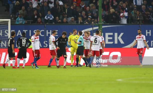 Players of hamburg argue with referee Guido Winkelmann after he awarded a penalty to Stuttgart following video referee decision during the Bundesliga...