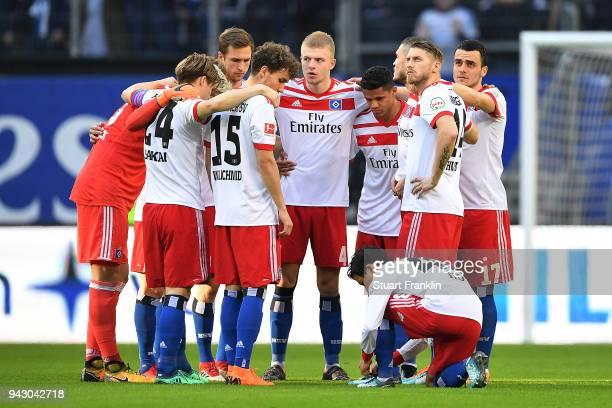 Players of Hamburg wait for Tatsuya Ito of Hamburg to finish lacing his shoes before the Bundesliga match between Hamburger SV and FC Schalke 04 at...