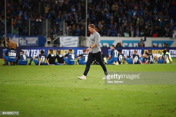 Players of Hoffenheim sit on the pitch to celebrate with their supporters as coach Julian Nagelsmann of Hoffenheim walks along the pitch after the...