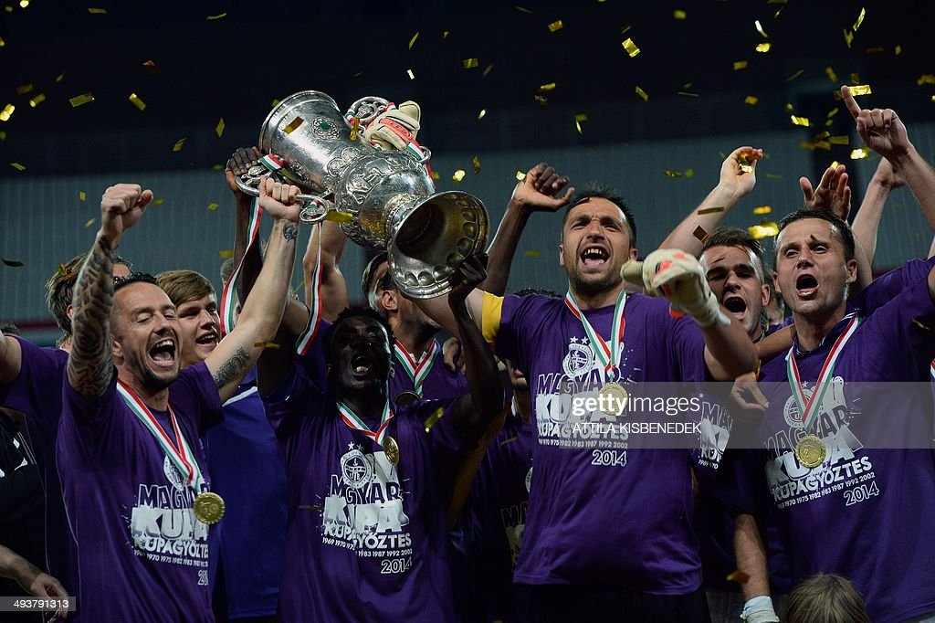 Players of Hungarian TE Ujpest celebrates their victory with the trophy after the Hungarian Cup final football match VTK Disosgyor vs TE Ujpest on May 25, 2014 at the Puskas stadium in Budapest. Ujpest won the match 6-5 after a penalty shootout.
