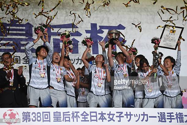 Players of INAC Kobe Leonessa celebrate their victory as captain Megumi Takase lifts the trophy after the 38th Empress's Cup Final between Albirex...
