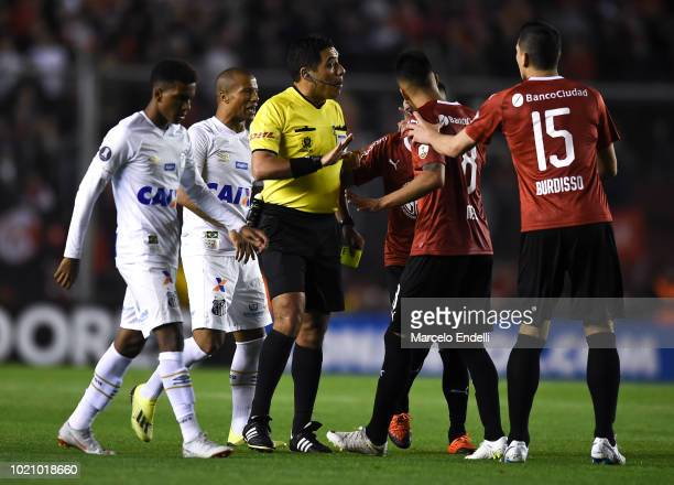Players of Independiente and Santos argue with referee Diego Haro of Peru during a round of sixteen match between Independiente and Santos as part of...