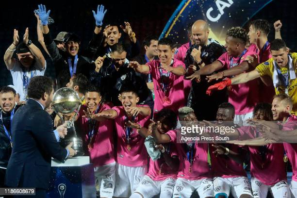 Players of Independiente celebrate with the trophy with teammates after winning the final of Copa CONMEBOL Sudamericana 2019 between Colon and...