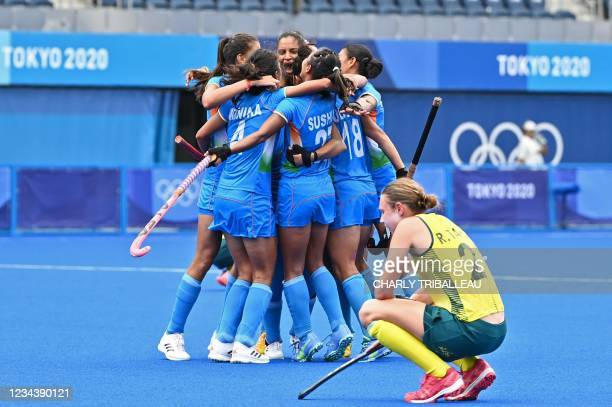 Players of India celebrate after defeating Australia 1-0 as Australia's Renee Taylor squats at the end of their women's quarter-final match of the...