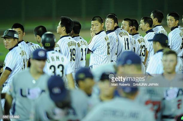 Players of Japan looks on as players of the USA celebrate after the bottom half of the nineth inning in the super round game between Japan and USA...