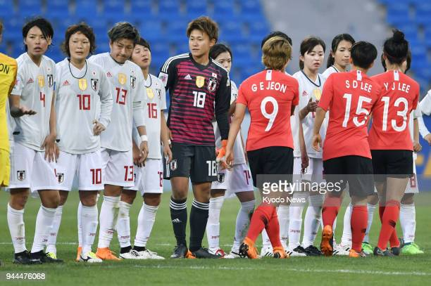 Players of Japan's national football team shake hands with players of the South Korean team after their scoreless draw in a Women's Asian Cup Group B...