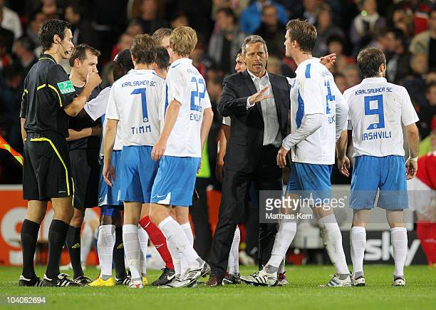 Players of Karlsruhe and head coach Markus Schupp discuss with the referees after the Second Bundesliga match between FC Energie Cottbus and...