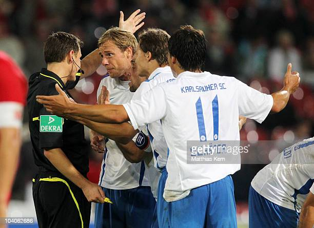 Players of Karlsruhe discuss with referee Florian Steuer during the Second Bundesliga match between FC Energie Cottbus and Karlsruher SC at Stadion...