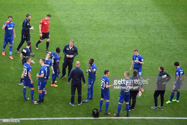 Players of Karlsruhe stand together as referee Christian Dingert suspended the match after fans of Karlsruhe threw flares onto the pitch during the...