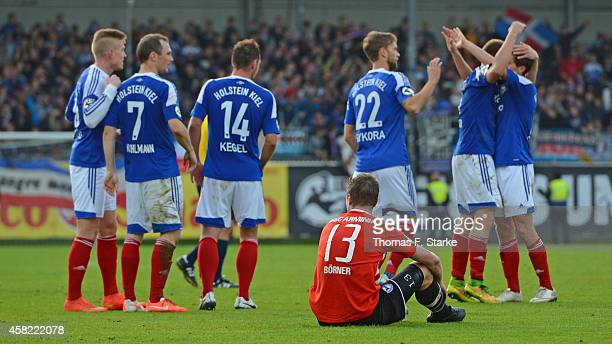 Players of Kiel celebrate in the background while Julian Boerner of Bielefeld sits dejected on the pitch after the Third League match between...