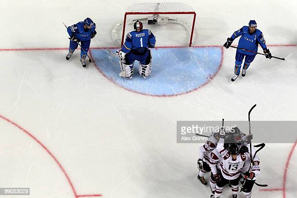 Players of Latvia celebrate a goal as John Parco goalkeeper Adam Russo and Michele Strazzabosco of Italy react during the IIHF World Championship...