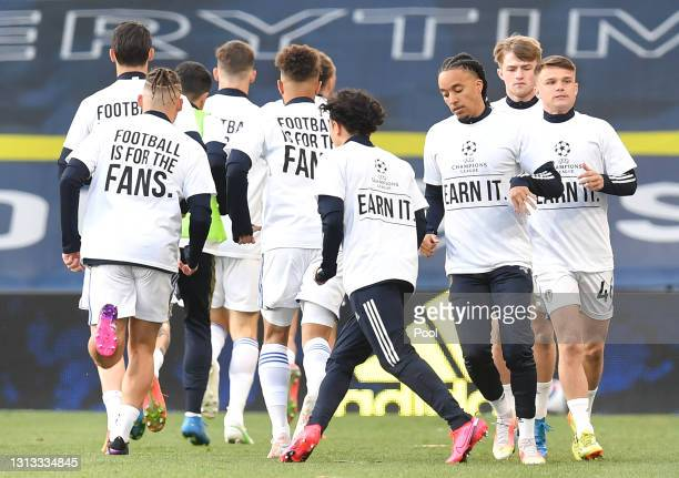 """Players of Leeds United warm up while wearing protest t-shirt's reading """"Football is for the fans"""" during the Premier League match between Leeds..."""