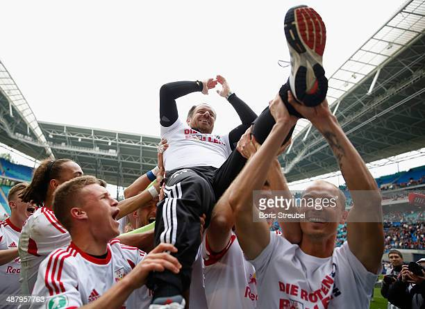 Players of Leipzig celebrate promotion to the second Bundesliga with their head coach Alexander Zorniger after the third league match between RB...