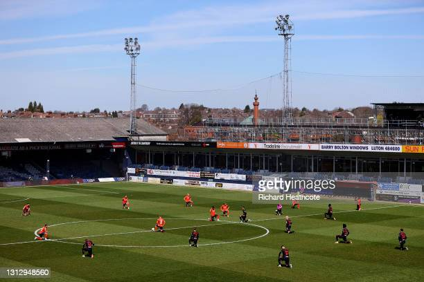 Players of Luton Town and Watford take a knee in support of the Black Lives Matter movement during the Sky Bet Championship match between Luton Town...