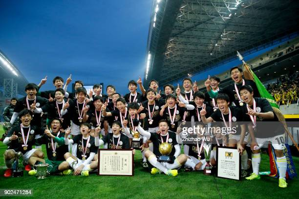 Players of Maebashi Ikuei celebrate for victory with trophy after the 96th All Japan High School Soccer Tournament final match between Ryutsu Keizai...