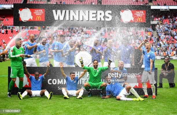 Players of Manchester City celebrate with the FA Community Shield following their team's victory in the FA Community Shield match between Liverpool...