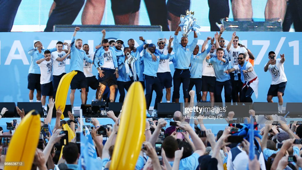 Players of Manchester City celebrates on stage while lifting the Premier League trophy during the Manchester City Trophy Parade on May 14, 2018 in Manchester, England.