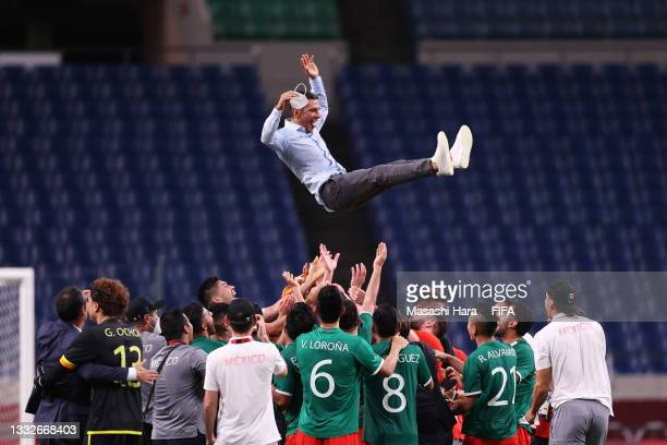 Players of Mexico throw Jaime Lozano, Head Coach of Mexico into the air after winning the Men's Bronze Medal Match between Mexico and Japan on day...