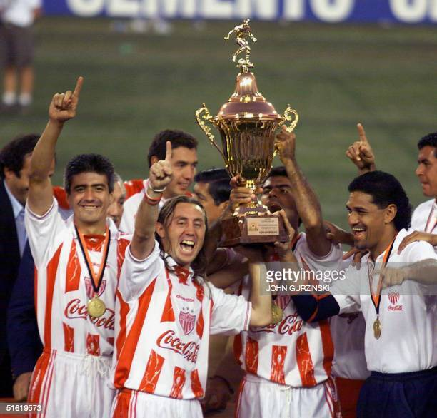 Players of Mexico's Necaxa hold their CONCACAF Champions Cup as they celebrate following their 2-1 win over Alajuela of Costa Rica 03 October 1999 in...